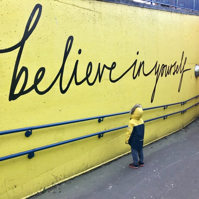 child looking at wall that says Believe in Yourself